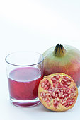 Pomegranate juice, half and full pomegranate on a white background