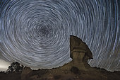 Rock formation in Los Monegros area in front of star trails during a clear february night, Aragon, Spain