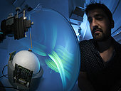 Apidologie - Alexis Buatois observes a new virtual system of visual learning for the bees. The bees are suspended in the locomotion compensator conceived for the analysis of their visual orientation. The bee, immobilized by the thorax, is placed on a hollow sphere of which the movements, induced by the walking of the bee, are recorded by optical sensors that allow for the reconstruction of the bee's trajectory. The bee walking on the compensator is exposed to visual stimuli present inside a cylindrical arena. The CRCA has shown that the cognitive capacities of recognition of visual forms by domestic bees are similar to those of humans and primates. This work was published in the revue Nature 2004. CNRS. Université Paul Sabatier. Toulouse.