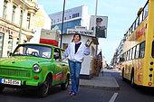 Apiculture urbaine - Erica Mayr, jeune femme de 37 ans pose avec une Trabant, une ruche et un enfumoir devant Check point Charlie. Cette jeune femme a fait un buzz médiatique en 2010 quand elle a posé ses premières ruches sur les toits d'un hangar à Berlin. Apicultrice depuis seulement 3 ans, Erica est propriétaire d'un bar branché dans le quartier de Kreuzberg. Aujourd'hui, Erica est heureuse car les abeilles et l'apiculture s'harmonise avec son métier et sa formation universitaire de paysagiste et d'horticulture. Germany