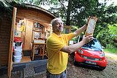 """Apiculture urbaine - Ralf Schneider Rathmann, 50 ans, possède quarante ruches dans Berlin. Ce passionné pose devant son rucher principal installé dans le cimetière de Luisen-Friedhof dans le quartier de Charlottenburg-Wilmersdorf. Dans le fond à gauche, la cabane d'extraction de Ralf où toutes les machines fonctionnent à l'énergie solaire. A droit, la Smart de Ralf est dédiée à l'apiculture. """"Berlin est un très bon endroit pour l'apiculture"""" nous déclare ce plombier de métier. Je produit près de 6 miels monoifloraux différent que je vends avec ma femme sur les marchés du week-end"""". Allemagne"""