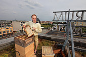"""Urban Beekeeping - Andreas Krüger, 42 years old, has set up his hives to the east, on the roof of the Hellersdorfer town hall on Alice Salomon square. Married with two children, he works as an instructor in an institution for the handicapped. He started beekeeping six years ago to satisfy an old childhood desire and to get back to nature. """"I also really wanted to make honey. I have a slogan, Honey before dogs…"""" He recounts that in Berlin it's better to have bees than a dog because the bees make it a good environment. """"Otherwise, I run marathons. I have ten hives and tomorrow I am going to harvest the honey from the hives on the Hellersdorfer town hall and I hope to get 80 kilos per hive"""". Germany"""