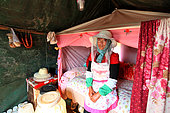 Honey Yellow Peril - Beekeeping and mass tourism on rapeseed field in Luoping, Yunnan. Luoping, Yunnan. A beekeeper in her tent, which is also her home for the eight months out of the year when the beekeepers travel from flowering field to flowering field. China