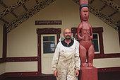 Miel Maori Manuka, Norman Parata à Ruatoria posant dans un costume d'apiculteur devant le marae de sa famille.