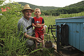 Ionel Farcas Cozmin, 54 years old, from Mures in Transylvania, with his grandson Catalin observes a hive on a scale and thus determines the nectar harvest for the day. When the quantity of nectar is no longer sufficient, it's time to break camp. Romanian traveling beekeepers, Romania
