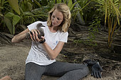 """Clare Keating Daly from the Arros research center of the """"Save our seas"""" foundation with a young Wedge-tailed Shearwater (Puffinus pacificus). Seychelles"""