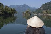 Young woman seen from behind with a conical hat, Lake Ba Be, Vietnam