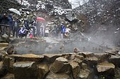 Tourists and Macaques of Japanese (Macaca fuscata) in hot spring, Snow Monkey Park, Joshinetsu Kogen, Japan
