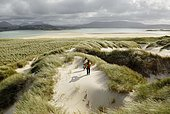 Hiking on sand dune at the shore of Mogarhathy at low tide, Co Donegal Ireland