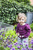 Little girl and Chive in bloom in a garden