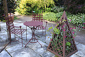 """""""The Purple Garden"""", paved terrace with iron furniture and pyramid where a Rose campion (Lychnis coronaria) grows, Jardins du Pays d'Auge, Cambremer, Calvados, Normandie, France"""