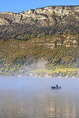 Fisherman in the morning mist on Lake Annecy in autumn, Haute Savoie, Alps, France