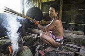 Man smoking his arrows after applying poison before going hunting, Pulau Siberut, Sumatra, Indonesia