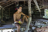 Man calling his pigs by hitting an open bamboo to feed them, pigs are free, Pulau Siberut, Sumatra, Indonesia