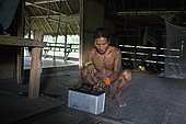 Man trying to connect a car battery to a light bulb before night, Pulau Siberut, Sumatra, Indonesia
