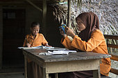 Girls revising before going to primary school, Pulau Siberut, Sumatra, Indonesia