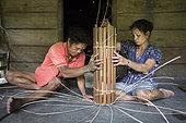 Couple making a traditional backpack, Pulau Siberut, Sumatra, Indonesia