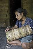 Woman making a traditional backpack, Pulau Siberut, Sumatra, Indonesia