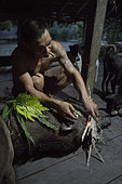 Man performing a ritual after killing a wild pig, Pulau Siberut, Sumatra, Indonesia