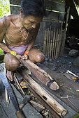 Man making poison for his arrows before hunting, Pulau Siberut, Sumatra, Indonesia