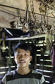 Portrait de Lagaï, 13 ans, posant dans la uma, en dessous de crânes de singe chassé par son père, Pulau Siberut, Sumatra, Indonésie