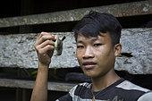 Garçon posant avec un petit oiseau de la famille des Nectariniidae qu'il a abattu au fusil et qu'il va manger, Pulau Siberut, Sumatra, Indonésie