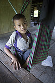 Child preparing for the siesta in his hammock, Pulau Siberut, Sumatra, Indonesia