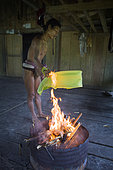 Man drying a banana leaf over the fire, Pulau Siberut, Sumatra, Indonesia