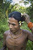Amantari, 39, dressed in a flower before a ceremony, Pulau Siberut, Sumatra, Indonesia