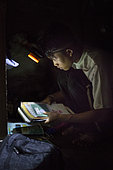 Lagaï, 13, preparing his satchel with a flashlight, Pulau Siberut, Sumatra, Indonesia