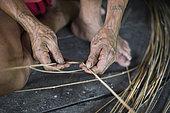 Man préparing rattan fibers to make a traditional backpack, Pulau Siberut, Sumatra, Indonesia