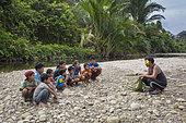 Teacher showing how to make a coconut palm basket, Pulau Siberut, Sumatra, Indonesia