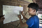 Mathematics exercise at the Sekolah Patas,an unofficial, non-governmental school, Pulau Siberut, Sumatra, Indonesia