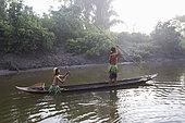 Women going to go fishing on their dugout made in a tree Meranti (Shorea sp.) at dawn, Pulau Siberut, Sumatra, Indonesia