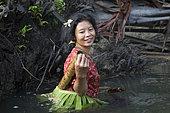 Woman fishing with a landing net, Pulau Siberut, Sumatra, Indonesia