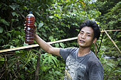 Patchouli oil producer showing a bottle full of patchouli oil, Pulau Siberut, Sumatra, Indonesia