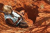 The Honey Ants Dream. Audrey Martin, a 59-year-old Aborigine woman digging with a burrowing stick, these days made of metal. Once made of acacia aneura wood, this stick was also used as much to dig up honey ants and tubers as to throw at prey such as lizards and other small animals. Northern Territory, Australia