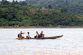 Boat on the water with 4 people on board, Doyang Hydroelectric Dam, where up to one million birds : Amur falcon (Falco amurensis) concentrate on the road to their migration to southern Africa, Nagaland, India