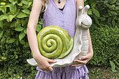 Girl holding a decorative snail in a garden in spring, Pas de Calais, France