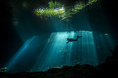 Scuba diver explores a cave in rays of light, Yucatan Peninsula, Mexico