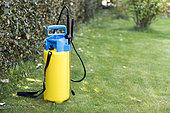 Sprayer placed on the lawn of a garden, before treatment of a hedge in Printemps, Pas de Calais, France