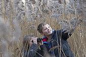 Teenage boy and girl birding in reedbed North Norfolk winter