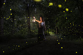 A girl is looking for the fireflies on a forest near the Po river in Italy