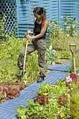 Woman gardening in an organic flowering vegetable garden