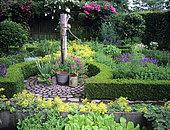 Ornate vegetable garden with Stork's bill (Erodium sp), Oregano (Origanum sp), Water pump, Garden of Mr and Mrs Deferme, Belgium.