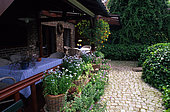 Table under canopy. Potted dishes. Paving. Honeysuckle and Ivy. Private garden. Belgium.