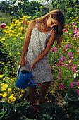 Girl watering. Child gardening in vegetable patch in summer