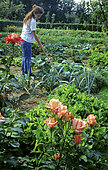 Young girl hoeing in a vegetable patch