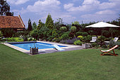 Garden with swimming pool and sitting area with lounge chair in summer, Belgium