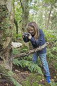 Young girl photographing nature in woodland North Norfolk in summer